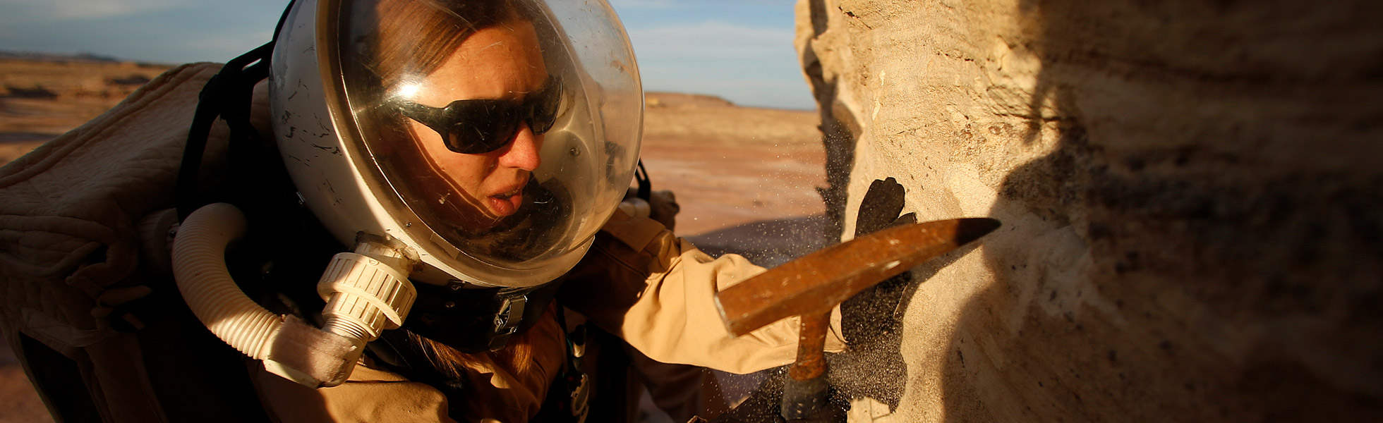 A photo of a woman in a space suit digging into a rock with a small hammer.